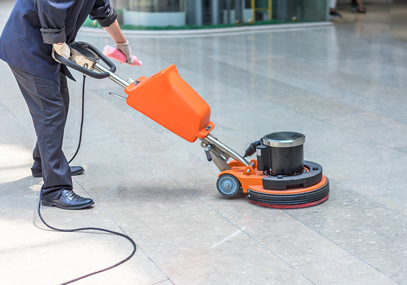 Man buffing floor with machine